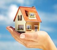 модел на къща в ръката на жена